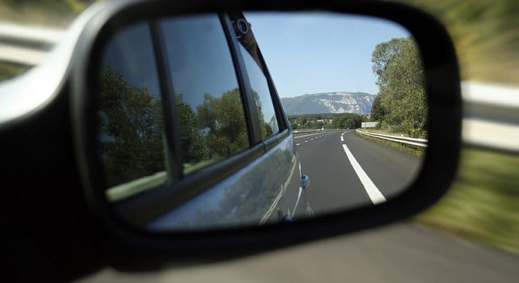 Car side-view mirror looking back on a highway